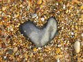 Heart-shaped granite rock on a pebble beach Royalty Free Stock Photo