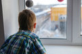 Close up view of little boy looking out of window Royalty Free Stock Photo