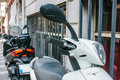 Close up view of motorized scooter parked on the sidewalk during daytime. Royalty Free Stock Photo