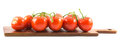 Close up view of red small cherry tomatoes on a wooden board and white background Royalty Free Stock Photo