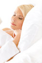 Close up view of sleepy woman in bed lying on the white cushion Royalty Free Stock Images
