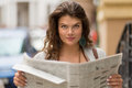 Close up view of tourist girl holding newspaper in her hands. Royalty Free Stock Photo