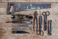 Close up view vintage rusted tools on old wooden table: pliers, pipe wrench, screwdriver, hammer, metal shears, saws and other Royalty Free Stock Photo