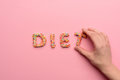 Close-up view of word diet made from sweets and human hand holding letter