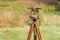 Close up of Vintage Surveyors Level (Transit, Theodolite) with wooden Tripod in a field. Royalty Free Stock Photo