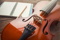Close up of violin and book on wooden table Royalty Free Stock Photo