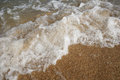 Close up wave on a sand beach, sea foam, splash of the sea Royalty Free Stock Photo