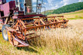 Close up of wheat harvesting machinery agricultural activities crops production with industrial combine Stock Image