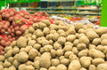 Close up of white and sweet potatoes on market stand. Royalty Free Stock Photo
