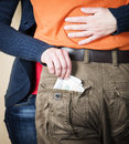 Close up of woman's hands embracing man and stealing taking out money out of his pocket. Woman stealing currency. Theft concept.