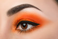 Close-up of woman eye with beautiful orange smokey eyes Royalty Free Stock Photo