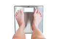 Close-up of woman feet weighing scale isolated on white backgrou Royalty Free Stock Photo