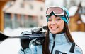 Close up of woman handing skis who thumbs up wearing sports jacket and goggles hands and Stock Image