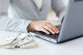Close up of woman hands with laptop and money Royalty Free Stock Photo