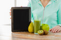 Close up of woman hands tablet pc and fruit juice Royalty Free Stock Photo