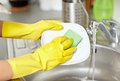 Close up of woman hands washing dishes in kitchen people housework and housekeeping concept protective gloves with sponge at Stock Images
