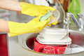 Close up of woman hands washing dishes in kitchen people housework and housekeeping concept protective gloves with sponge at Royalty Free Stock Photography