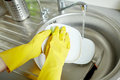 Close up of woman hands washing dishes in kitchen people housework and housekeeping concept protective gloves with sponge at Stock Photos