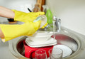 Close up of woman hands washing dishes in kitchen people housework and housekeeping concept protective gloves with sponge at Stock Photo