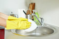 Close up of woman hands washing dishes in kitchen people housework and housekeeping concept protective gloves with sponge at Stock Photography
