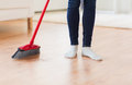 Close up of woman legs with broom sweeping floor Royalty Free Stock Photo