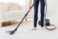 Close up of woman legs with vacuum cleaner at home Royalty Free Stock Photo