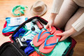 Close up of woman packing travel bag for vacation summer tourism and objects concept Royalty Free Stock Image