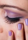 Close up of woman s eye with purple eyeshadow and finger nail varnish Royalty Free Stock Image