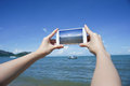 Close up of woman's hand holding smart phone, mobile, smart phone over blurred beautiful blue sea and fishing boat Royalty Free Stock Photo