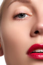 Close-up of woman's lips with bright fashion red glossy makeup. Macro bloody lipgloss make-up. Red lips. Open mouth