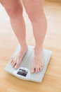 Close up of woman standing on weighing scale in a fitness studio Stock Photography