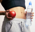 Close up woman stomach with hands holding water and reg apple isolated Royalty Free Stock Photography