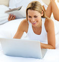 Close-up of woman using a laptop lying on bed Stock Images