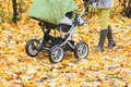 Close-up of woman walking in autumn park with stroller Royalty Free Stock Photo