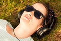 Close up of woman wearing headphones and listening to music top view with sunglasses Stock Images