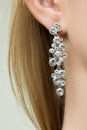 Close up of woman wearing shiny diamond earrings Royalty Free Stock Photo