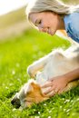Close up of woman who strokes retriever golden lying on the green grass in the park Stock Photography