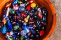 Colorful glass beads of various shapes and sizes placed inside a wooden bowl Royalty Free Stock Photo