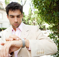 Close up of a young attractive businessman looking at the time in his watch while standing in a classic city street outdoors Stock Image