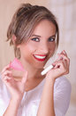Close up of young beautiful smiling woman holding a menstruation cotton tampon in one hand and with her other hand a