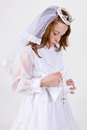 Close up young girl her first communion dress veil pulling her rosary beads cross purse Royalty Free Stock Photo