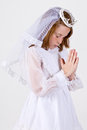 Close up young girl praying her first communion dress veil Stock Photos