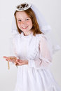 Close up young girl smiling her first communion dress veil holding her rosary beads cross Stock Photos