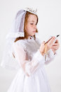 Close up young girl smiling her first communion dress veil reading bible holding her rosary beads cross Royalty Free Stock Photo