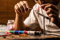 Close up on young man s hands tying a fly for fishing as he is carefully using red feather Royalty Free Stock Images
