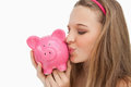 Close-up of a young woman kissing a piggy-bank Stock Photography