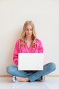 Close up of young woman sitting on floor and using laptop portrait in living room Royalty Free Stock Images