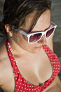 Close up of a young woman wearing a bikini top shot red and white polka dot and white sunglasses Royalty Free Stock Image