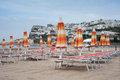 Closed beach umbrellas and deck chairs on an empty beach Royalty Free Stock Photo
