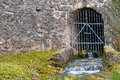 Closed gate into the dungeon view a secret passageway which leads to a of an old fortress where now a creek flows through german Royalty Free Stock Photos